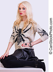 Pretty fashionable blonde girl sitting on chair