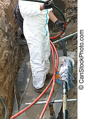 expert electrician in road excavation during the repair job of a large high voltage power cable