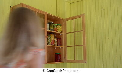 woman canned food shelf - Woman put pot canned pickled food...