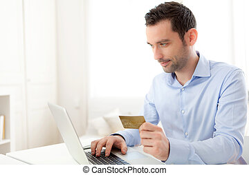 Young business man paying online with credit card - View of...