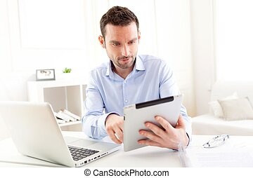 Young business man working at home on his tablet - View of a...