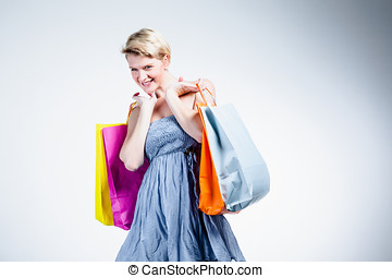 Portrait of a blonde woman holding bags