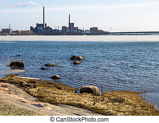 City beahind the ocean - Industrial landscape over a rocky...