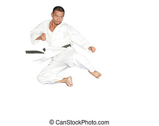 Black belt karate man jumping to give a high kick