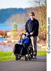 Father walking with disabled son in wheelchair