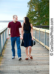 Young happy interracial couple walking together on wooden pier over lake