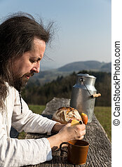 bearded man is snacking in the nature - a bearded man is...