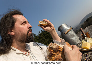 rustically man with long hair eating bread in the nature