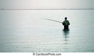 fisherman with rod  in the water fi