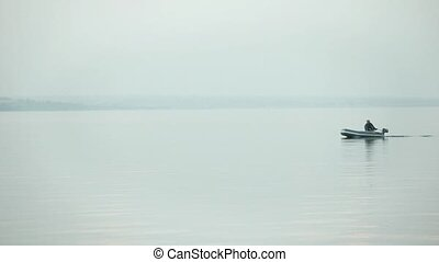 Fishing boat morning on the lake - fisherman floats in a...