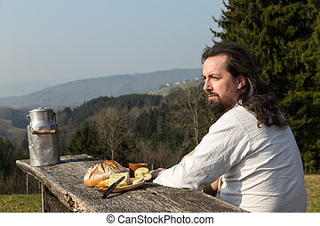 rustically long-haired man is snacking healthy food