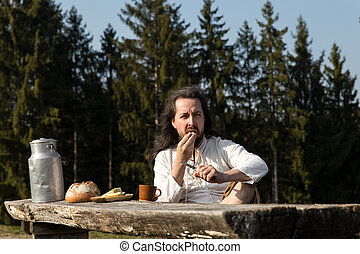 rustically man making a picnic in the nature - a rustically...