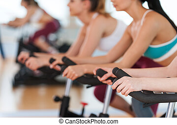 Exercising on gym bikes. Cropped image of tree young women in sports clothing exercising on gym bicycles