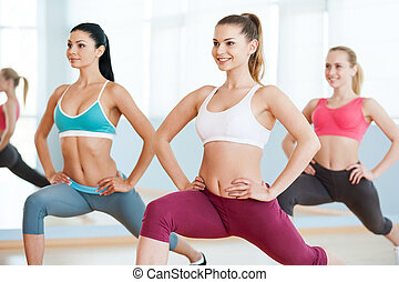 Girls on aerobics class. Three beautiful young women in...