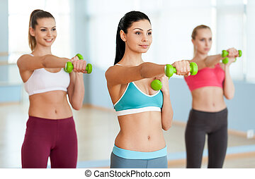 Exercising with dumbbells. Three beautiful young women in sports clothing exercising with dumbbells and smiling