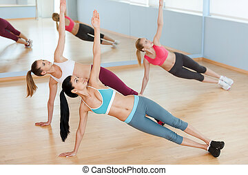 Women on aerobics class. Top view of three beautiful young women in sports clothing stretching