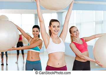Women with fitness balls. Three beautiful young women in sports clothing exercising with fitness balls and smiling at camera