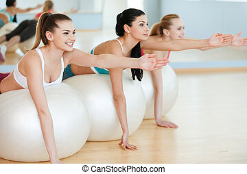 Training with fitness balls. Three beautiful young women in sports clothing exercising on fitness balls and smiling