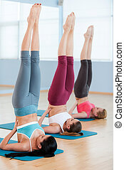 Women stretching. Three beautiful young women in sports clothing raising their feet up while lying on exercise mats