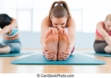 Stretching exercise. Three beautiful young women in sports clothing stretching while sitting on exercise mats