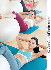 Preparing bodies for summer season. Top view of three beautiful young women in sports clothing exercising with fitness ball while lying on exercise mats and looking at camera
