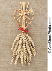 Corn Dolly - Corn dolly with red bow over old brown paper...