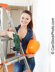 Happy girl with drill and hardhat