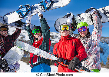 Four friends holding snowboards and skies - Four happy...
