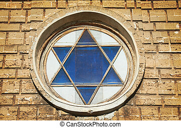 Blue star of David in the window. Yellow wall at background
