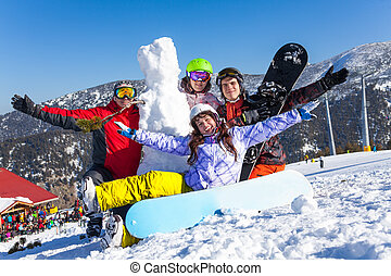 Four happy friends with snowboard and snowman - Four smiling...