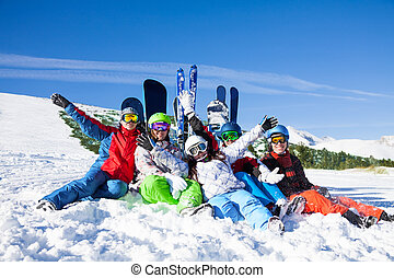 Happy friends sitting with snowboards and skis - Five happy...