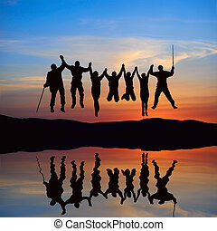 Silhouette of jumping friends on the beach with reflection...