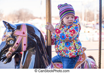 Little happy girl riding on carousel at an amusement park
