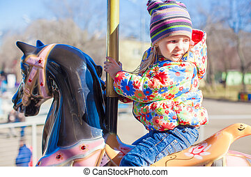 Little happy girl ride on carousel at an amusement park