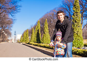 Portrait of adorable little girl and happy father ride on...