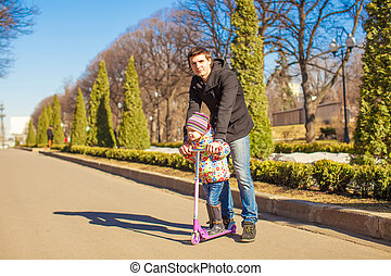 Adorable little girl and happy father walking in spring park on a sunny day