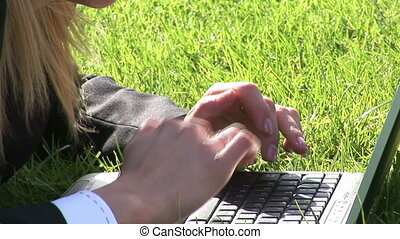 Woman lying on grass using laptop computer - Stock Video...