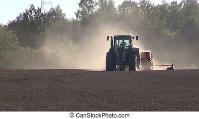 tractor seeding grain crop on field