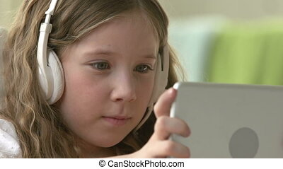 Vacations Occupation - Little girl in earphones using...