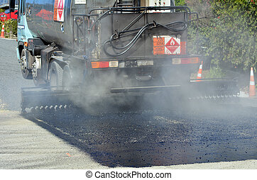 Tar truck vehicle tarring a piece of new road during...