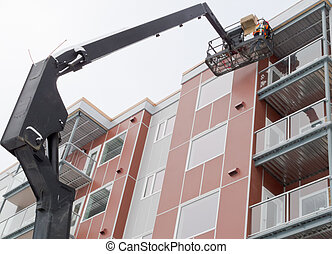 Boom lift worker work apartment highrise exterior - Workmen...