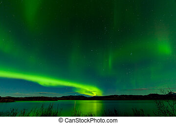 Aurora borealis show Lake Laberge surface mirrored -...