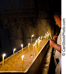 Holy Sepulcher in Jerusalem Man puts a candle