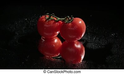 Two red tomatoes on dark background close-up and master shot