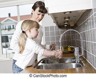 Drinking water - Small Girl in the kitchen with her mother...