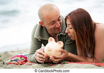 Budget holidays  - young couple holding a piggy bank