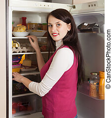 Brunette woman looking in refrigerator
