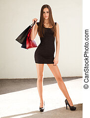 Stylish shopper. - Portrait of a slender young brunette...