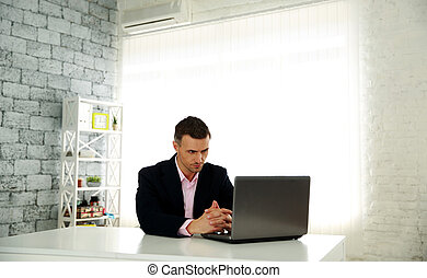 Handsome businessman sitting at the table with laptop in office