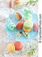 Colorful macaroons on blue plate and little easter bunnies